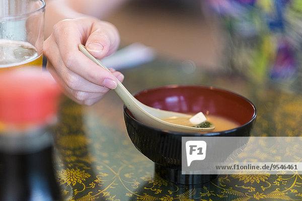 Junge Frau isst japanische Misosuppe