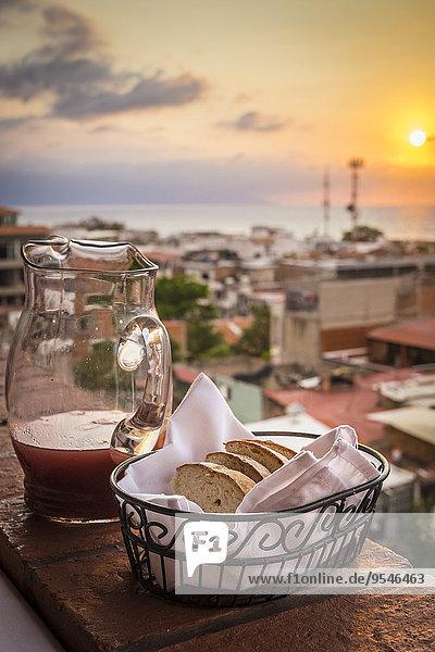 Mexiko  Jalisco  Blick auf Puerto Vallarta vor Sonnenuntergang  Brotkorb und Karaffe auf Balustrade