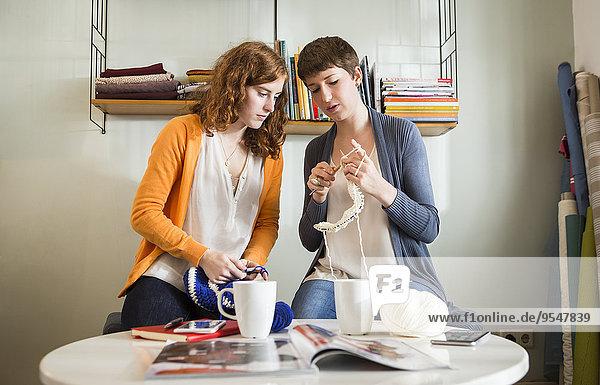 Zwei junge Frauen  die ihre Freizeit mit Stricken verbringen