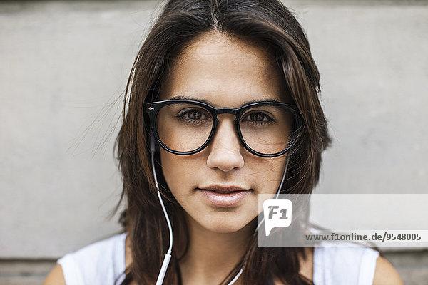 Porträt einer jungen Frau mit Ohrhörern in schwarzer Brille