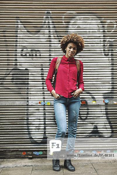 Lächelnde junge Frau steht vor dem Rollladen mit Graffiti