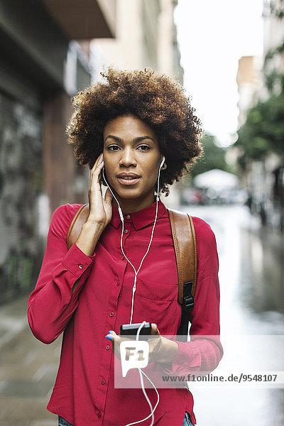 Porträt einer jungen Frau  die Musik mit Kopfhörern hört