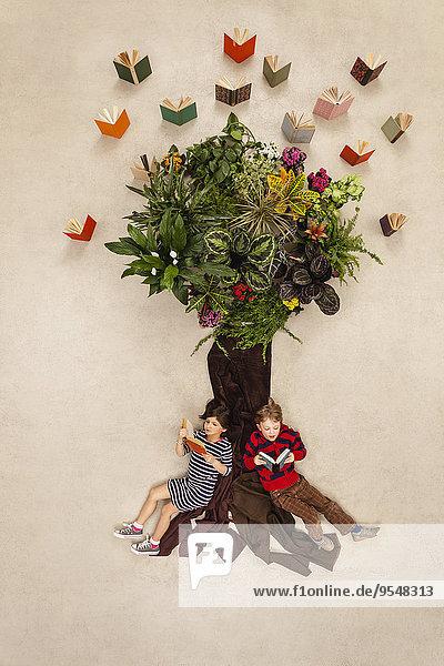 Junge und Mädchen sitzen und lesen unter dem Buchbaum