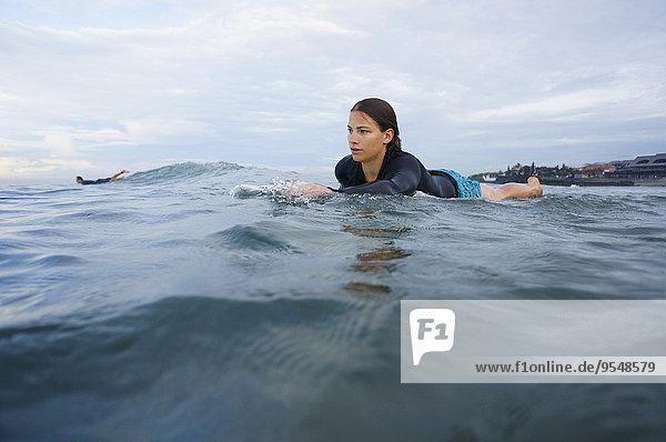 Indonesien  Bali  Canggu  junge Frau auf dem Surfbrett liegend  auf dem Weg nach vorn