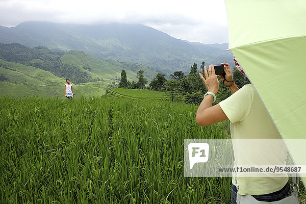 China  Guangxi  mother taking picture of daughter in rice field