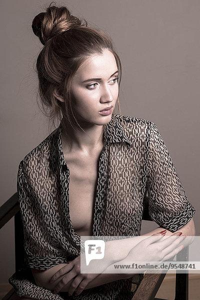 Porträt einer jungen Frau mit gemustertem Hemd und Brötchen