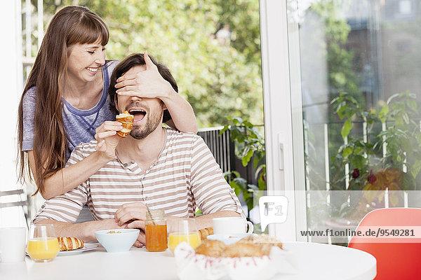 Frau füttert Mann am Frühstückstisch Frau füttert Mann am Frühstückstisch