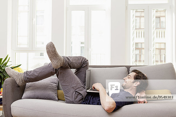 Entspannter Mann auf der Couch liegend mit Laptop