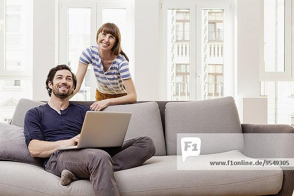 Lächelndes Paar mit Laptop zu Hause