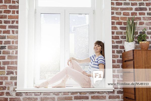 Entspannte Frau auf der Fensterbank sitzend