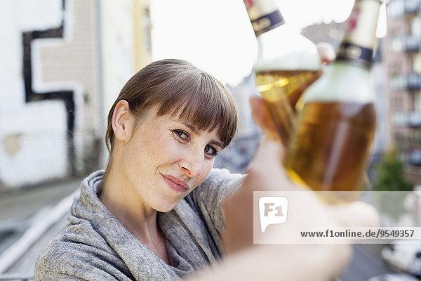 Lächelnde Frau auf dem Balkon klirrende Bierflasche