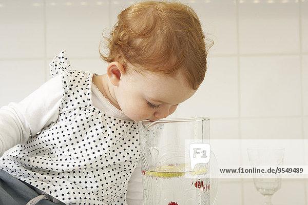 Little girl watching lemon slices at water carafe