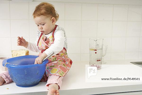 Kleines Mädchen sitzt auf der Küchentheke mit Rührschüssel