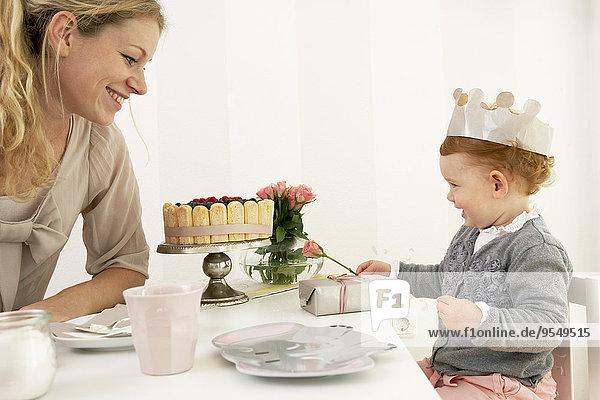 Mutter und Tochter feiern den ersten Geburtstag des kleinen Mädchens