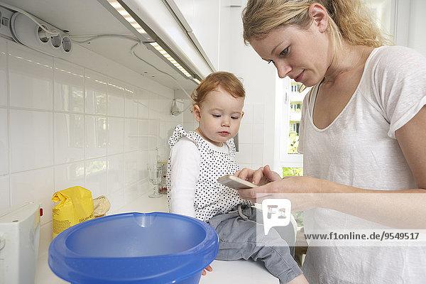 Mutter und kleine Tochter backen gemeinsam Kuchen