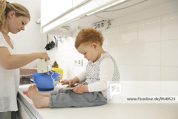 Kleines Mädchen sitzt auf der Küchentheke mit Smartphone  während ihre Mutter backt