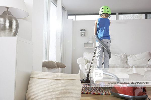 Boy in living room tangled in vacuum cleaner