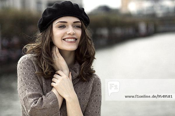 Porträt einer glücklichen jungen Frau mit Baskenmütze und Strickkleid