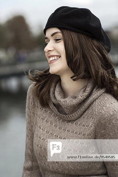 Porträt einer lächelnden jungen Frau mit Baskenmütze und Strickkleid
