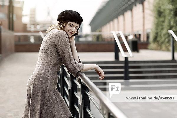 Porträt einer jungen Frau mit Baskenmütze und Strickkleid an einem Geländer lehnend