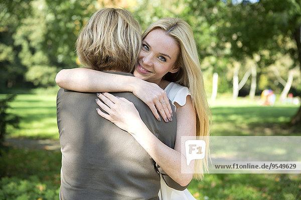 Mutter und erwachsene Tochter umarmend im Park