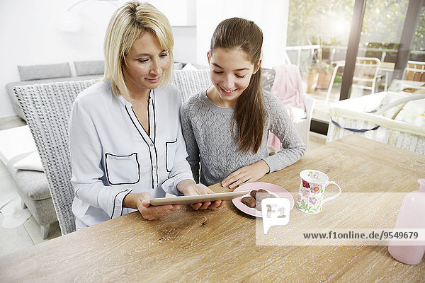 Mother and daughter eating cookies  watching digital tablet