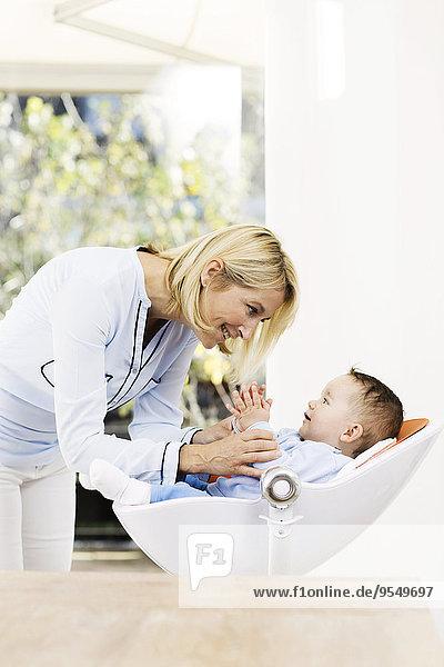 Mutter spielt mit dem Jungen auf dem Sitz