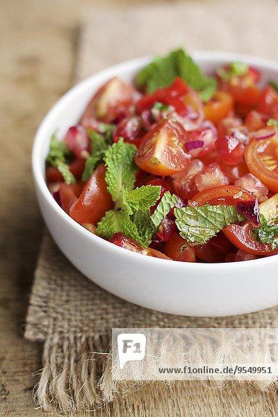 Schüssel mit Tomaten- und Granatapfelsalat  garniert mit Minzblättern auf Jute und Holz Schüssel mit Tomaten- und Granatapfelsalat, garniert mit Minzblättern auf Jute und Holz