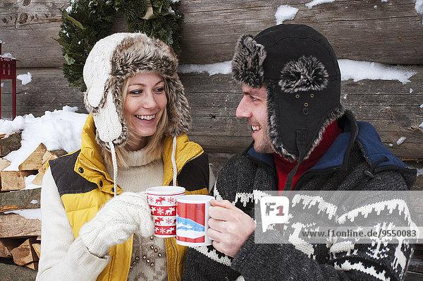 Paar klirrende Tassen an der Holzhütte im Winter