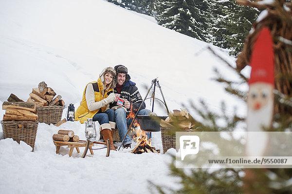Lächelndes Paar im Schnee am Lagerfeuer