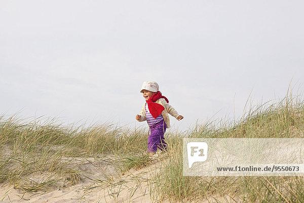 Happy little girl running on a beach dune