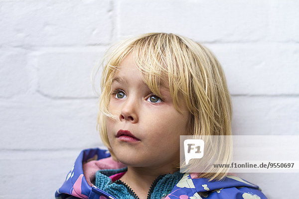 Portrait of sad little girl in front of whie wall