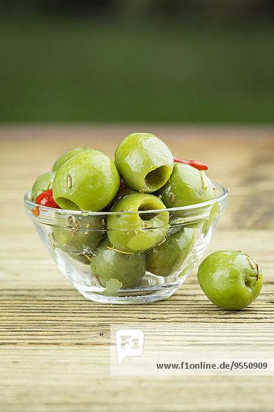 Glasschale mit marinierten grünen Oliven auf Holz