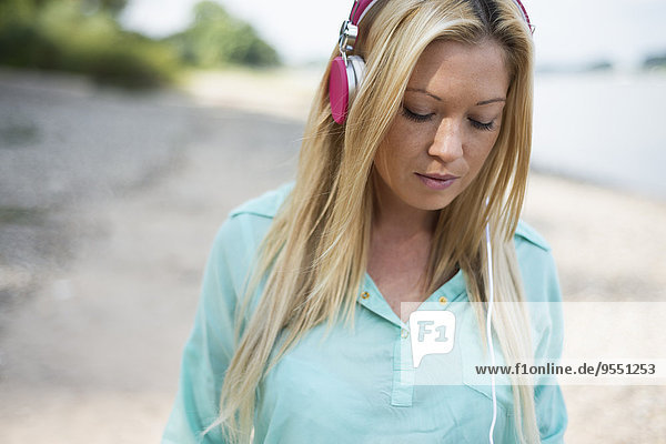 Junge Frau mit Kopfhörer am Strand
