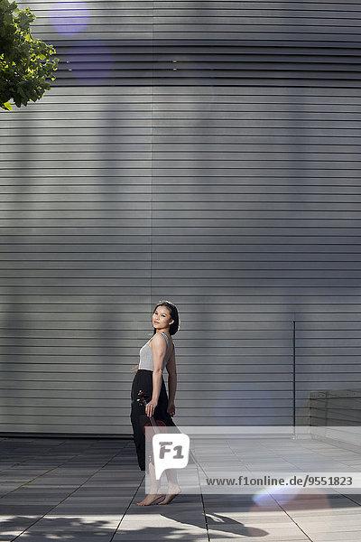 Junge Asiatin mit Geige vor einer Fassade stehend