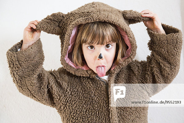 Portrait of little girl masquerade as a bear making a face