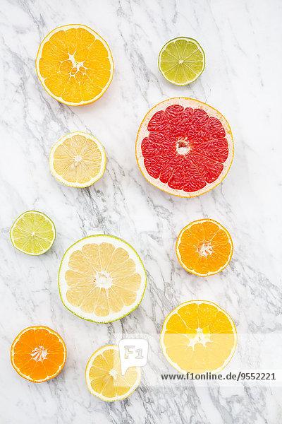 Scheiben verschiedener Zitrusfrüchte auf weißem Marmor Scheiben verschiedener Zitrusfrüchte auf weißem Marmor
