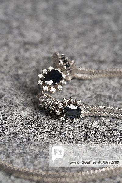 Halskette aus Weißgold mit Saphiren und Diamanten auf grauem Stoff