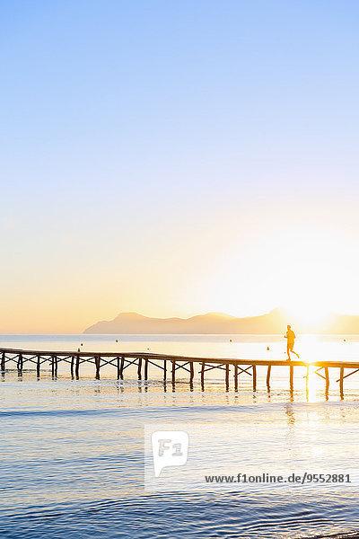 Spanien  Balearen  Mallorca  Mann beim Joggen am Steg bei Sonnenaufgang