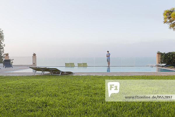 Spanien  Balearen  Mallorca  ein Teenager  der sich auf eine Sicherheitsglasschiene hinter einem Swimmingpool stützt.