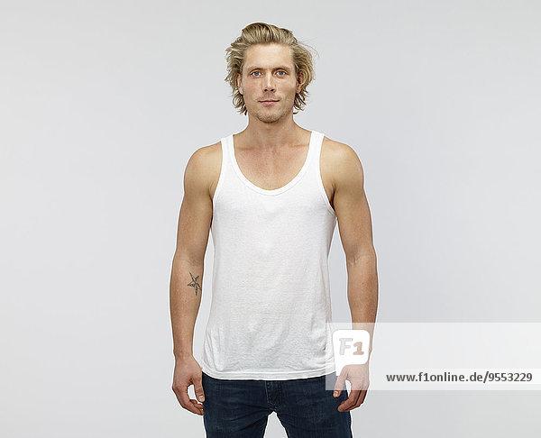 Porträt eines jungen blonden Mannes mit Weste vor weißem Hintergrund