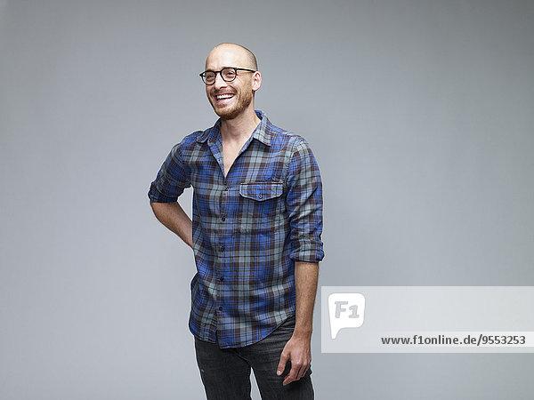 Porträt des lachenden Mannes mit der Hand auf der Hüfte vor grauem Hintergrund