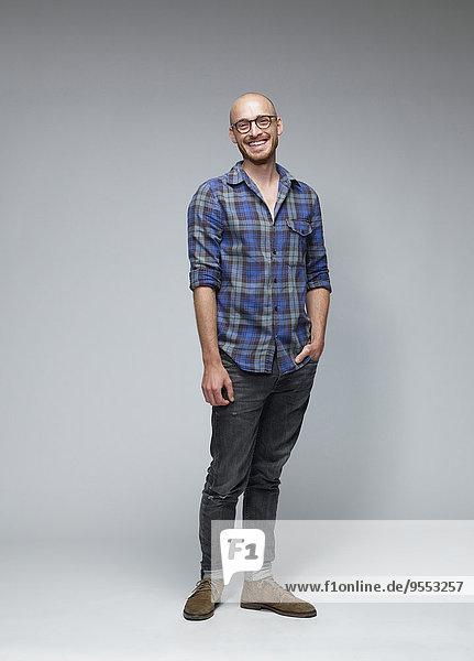 Porträt des lachenden Mannes mit der Hand in der Tasche vor grauem Hintergrund