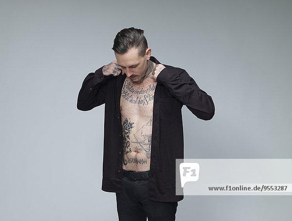 Mann mit Tätowierung auf der Taille und schwarzem Hemd vor grauem Hintergrund.