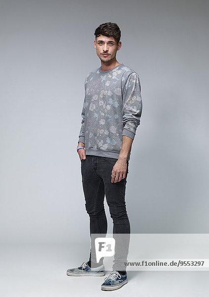 Porträt eines jungen Mannes mit gemustertem Sweatshirt vor grauem Hintergrund