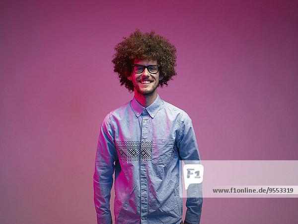 Porträt des lächelnden jungen Mannes mit Afro vor rosa Hintergrund