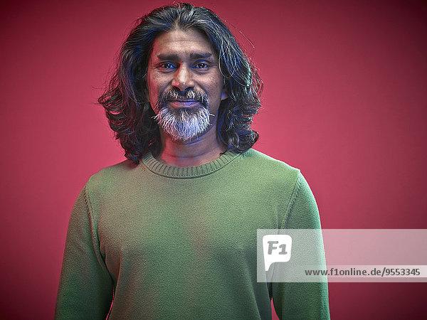 Porträt eines lächelnden Mannes vor rotem Hintergrund