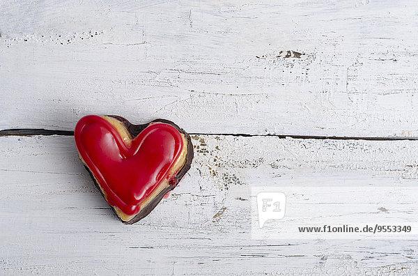 Herzförmiger Biskuitkuchen auf weißem Holz