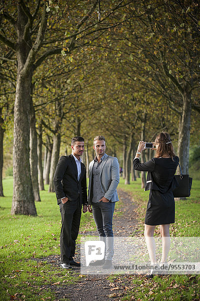 Junge Geschäftsfrau beim Fotografieren von Geschäftspartnern mit ihrem Smartphone im Park