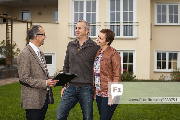Estate agent with potential buyers in front of residential house